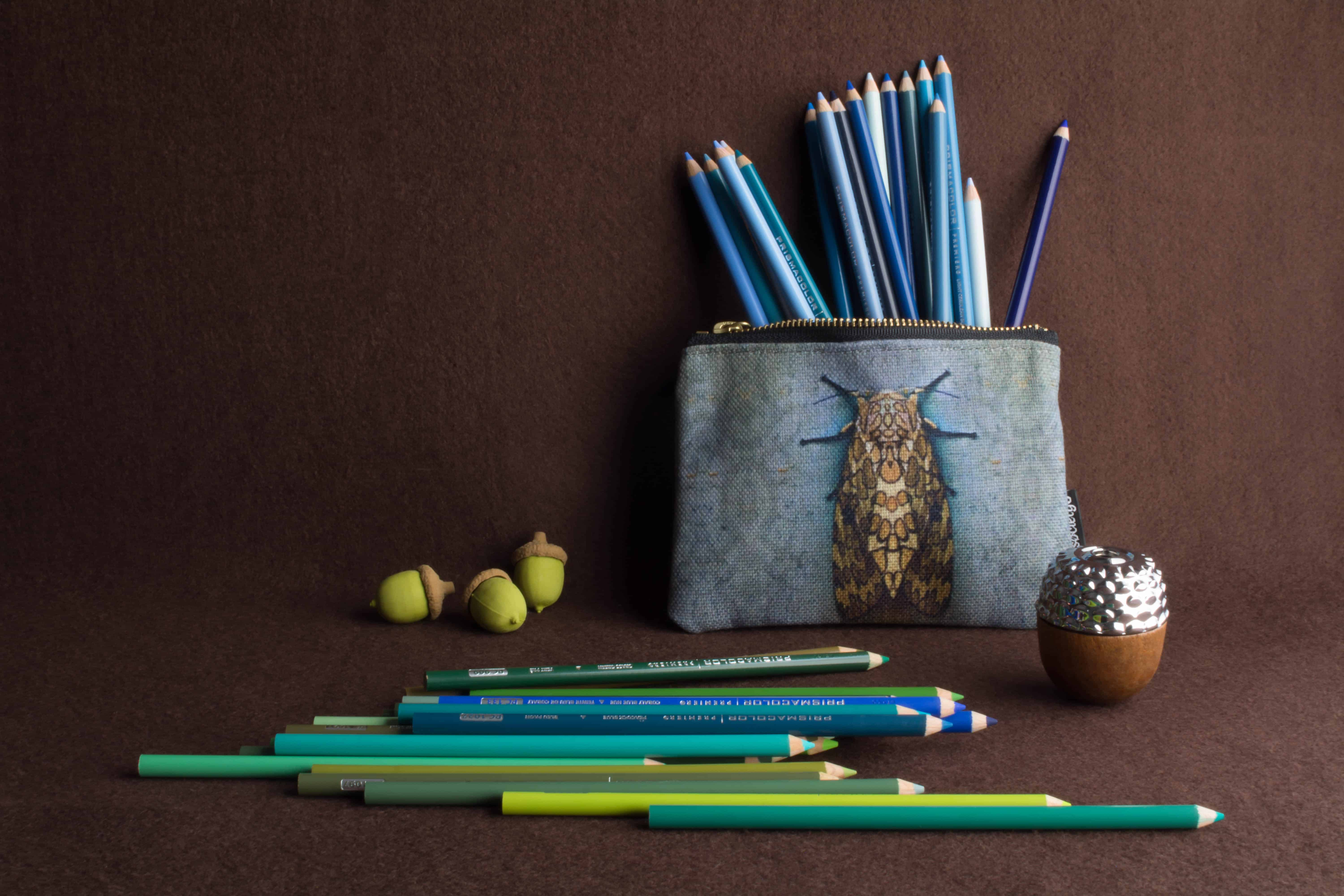 Photo of a still life with Prismacolor Premier Colored pencils, erasers, and acorn-shaped pencil sharpener.