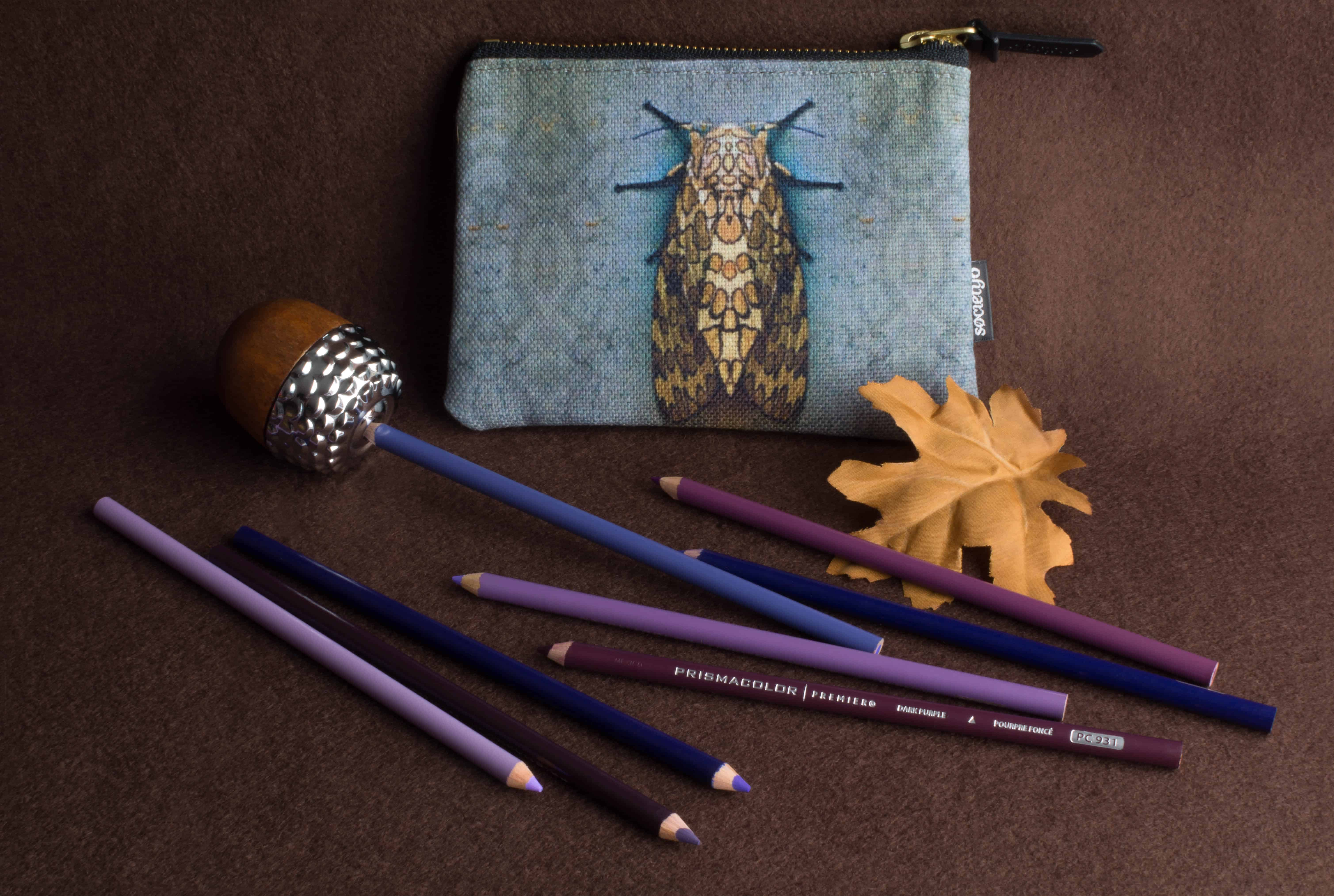 Photo of a still life with prismacolor colored pencils, a pencil pouch, a pencil sharpener, and an autumn leaf.