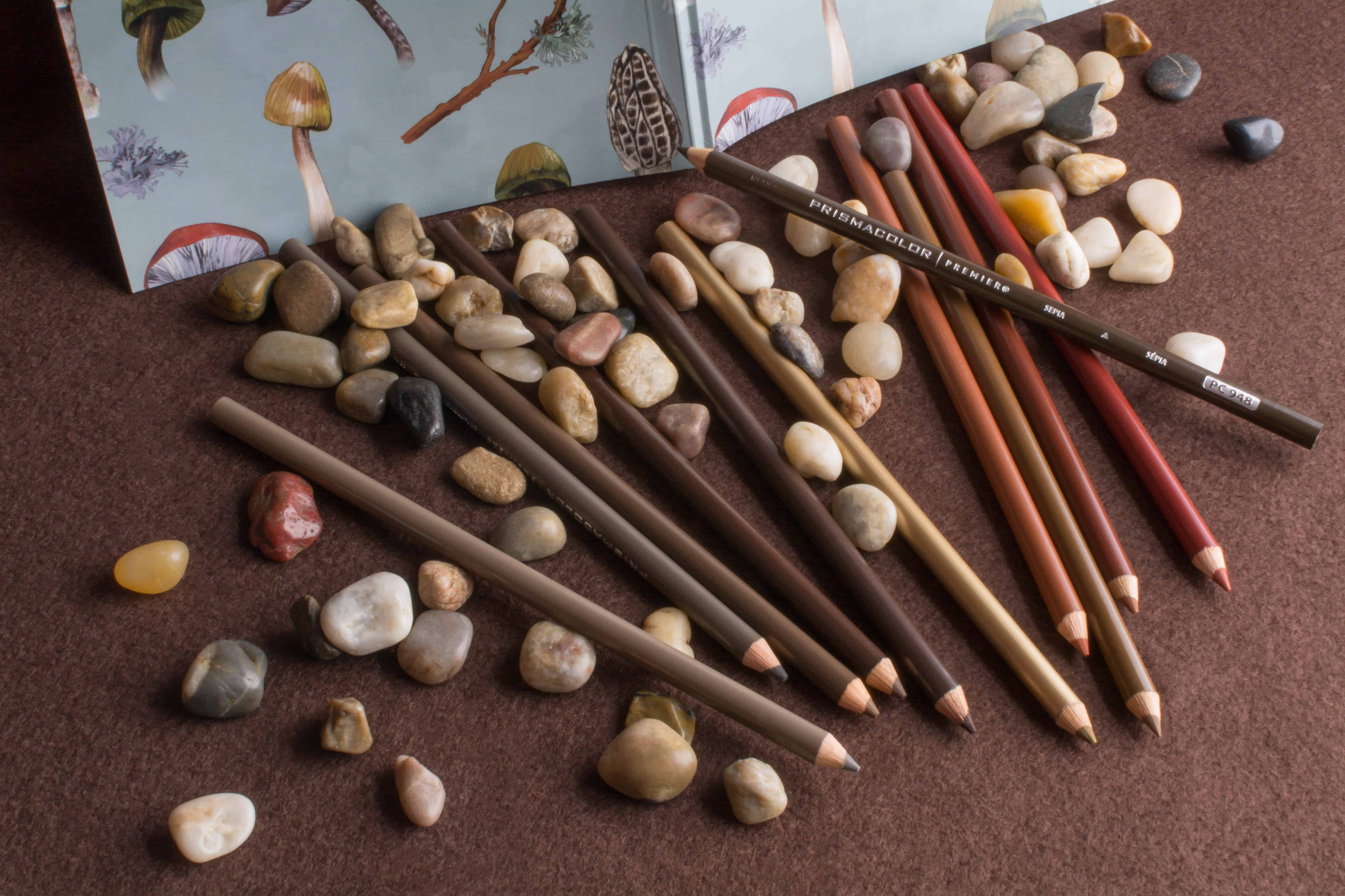 Photograph of brown prismacolor colored pencils on brown felt with small stones and pebbles.