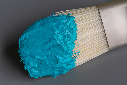 Close-up photo of turquoise Winsor and Newton Artists' Oil Color on a paintbrush.